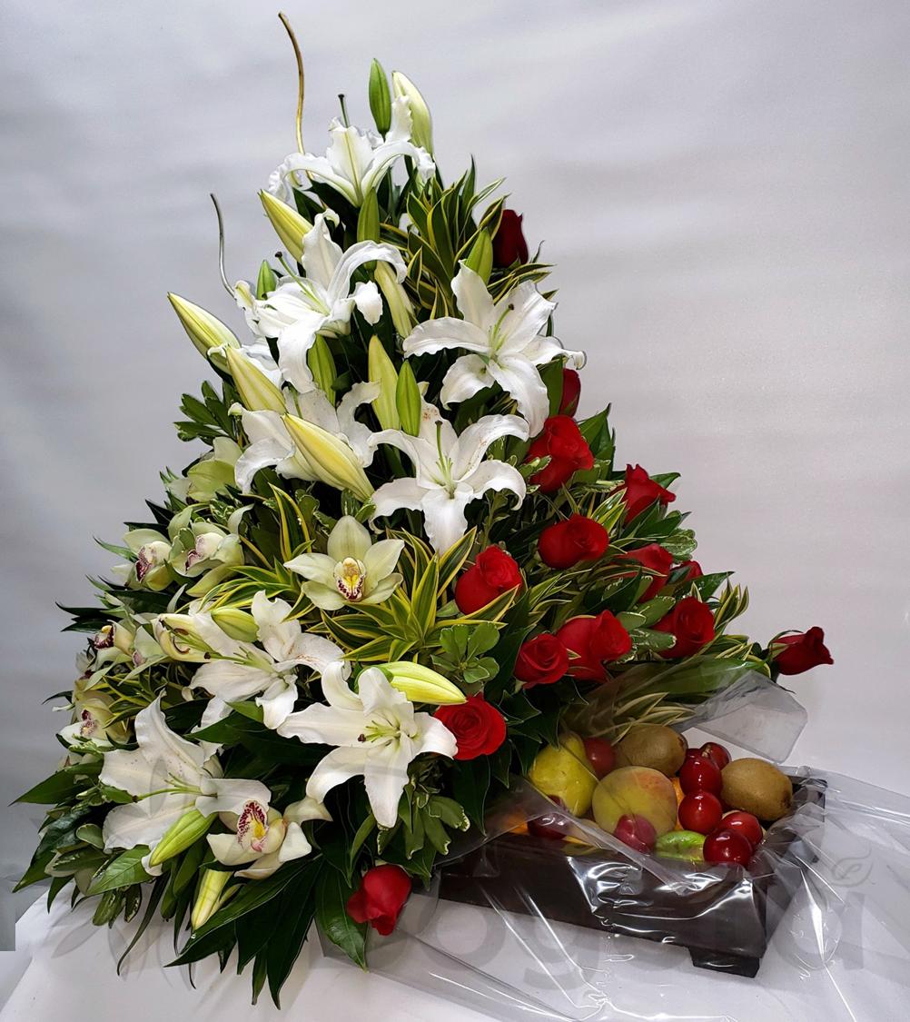 Arreglo con frutas, rosas, orquideas y lirios